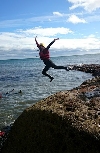 Image of woman in red and black wetsuit with yellow helmet jumping from rocks into sea on coasteering adventure
