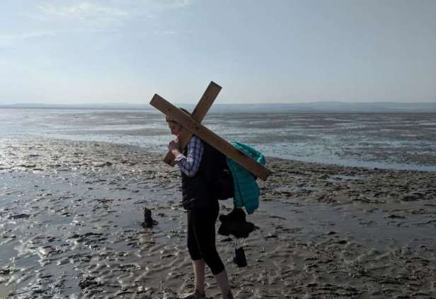 Image of woman walking barefoot in mudflats carrying wooden cross along pilgrims causeway to Holy Island