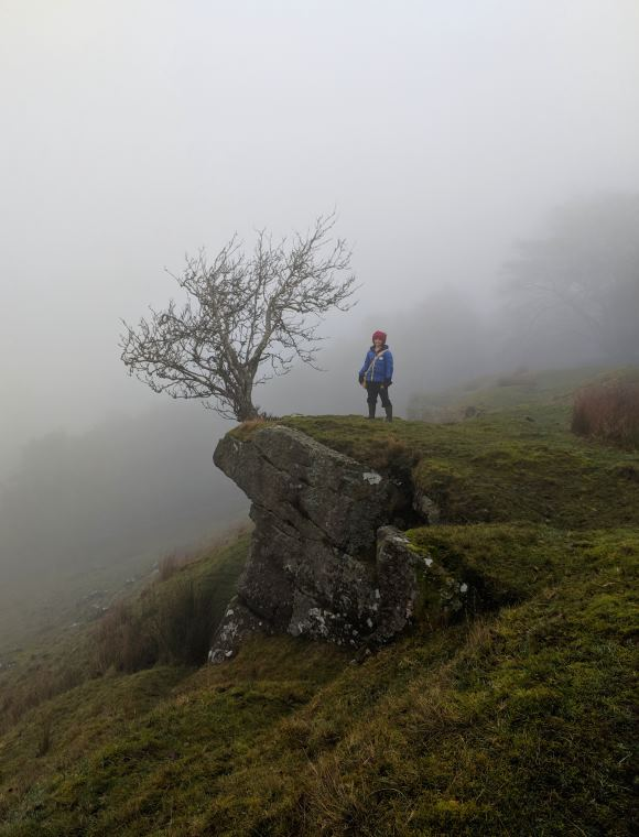Image of child in outdoor gear stood on remote ridge in atmospheric mist next to bare tree