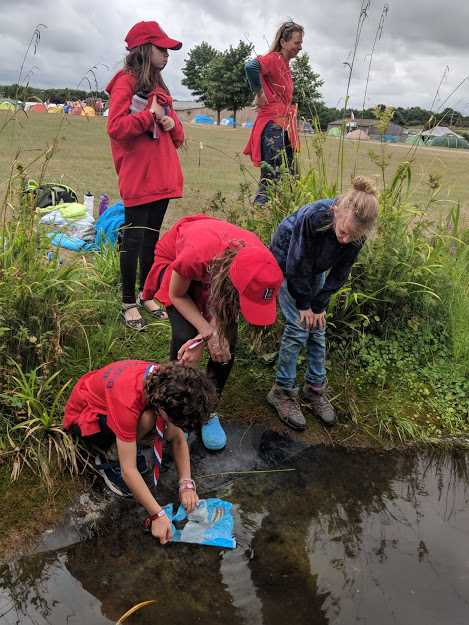 Image of group of children in red tops pond dipping at the bank of a small pool with grass and tents in far background