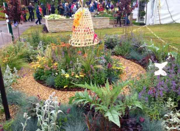 Image of wicker bell hanging from pole in centre of circular flower bed with plants and white butterfly with crowd of people behind
