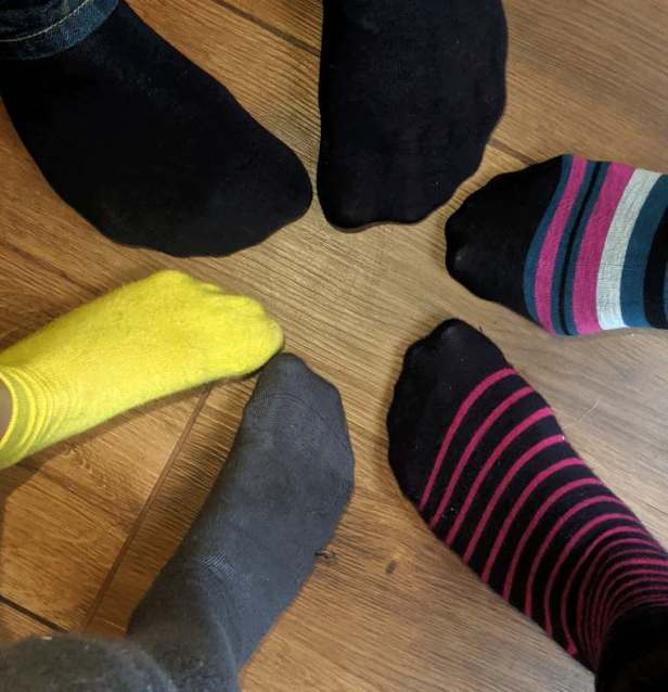 Image of 3 different sized pairs of feet in a circle wearing multicoloured socks