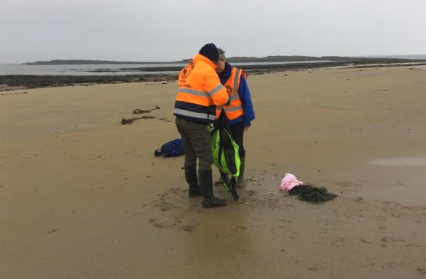 Image of man and woman on beach in high visibility jackets holding bag containing grey seal pup for weighing