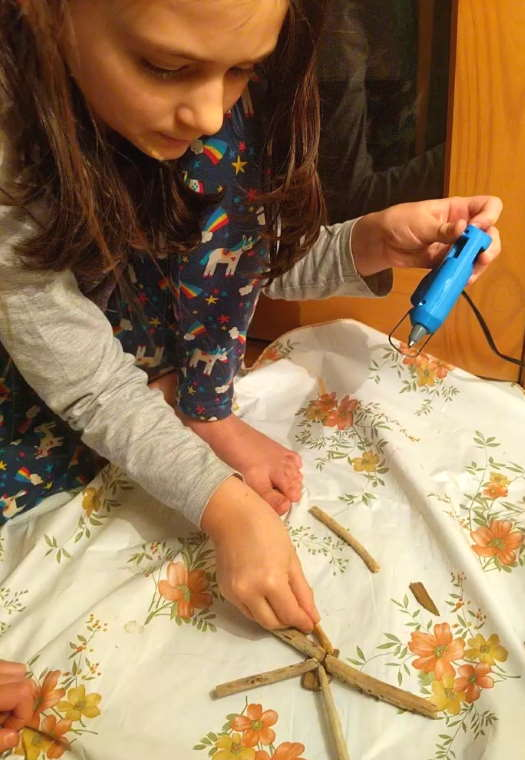 Image of girl using blue glue gun to stick pieces of driftwood into star shape