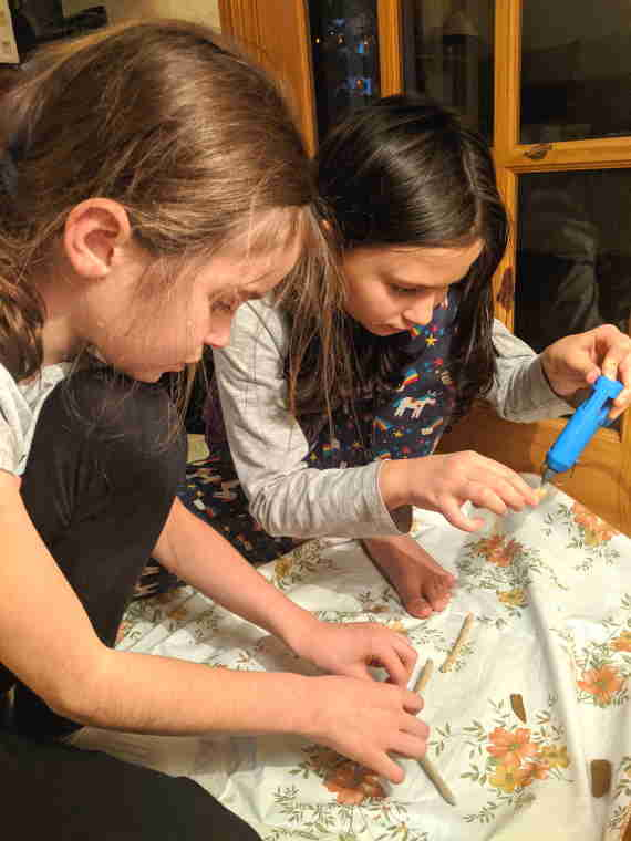 Image of two girls sat on floor making driftwood stars with sticks and a glue gun