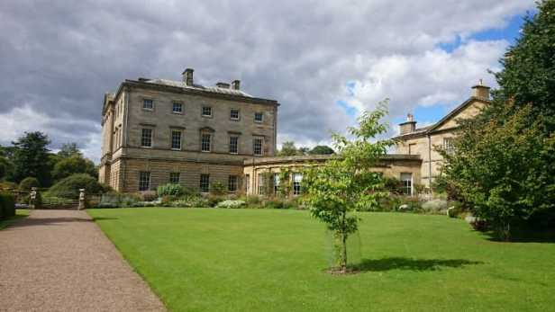 Image of Howick Hall stately home on sunny day with gardens and lawn to front