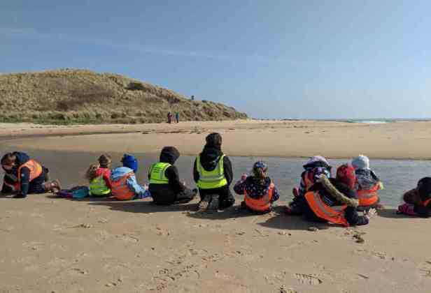 Class of children in high vis jackets sat on beach with backs to camera in front of estuary