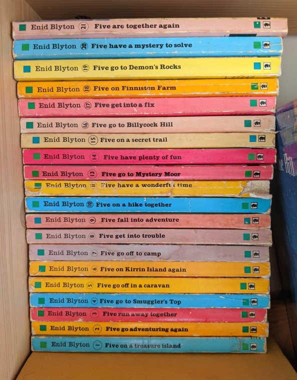 Image of full collection of brightly coloured Famous Five books by Enid Blyton stacked on a shelf