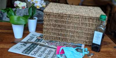 Wicker basket used as a time capsule container with newspaper in front, coins, medicine bottle, medical face mask and orchids
