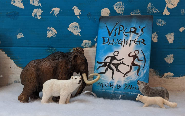 Blue Viper's Daughter book cover in front of snow painted sky scene with mammoth, polar bear, wolf and arctic fox models