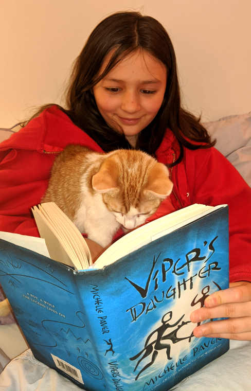 Girl in red top with ginger and white cat on lap reading copy of Viper's Daughter by Michelle Paver