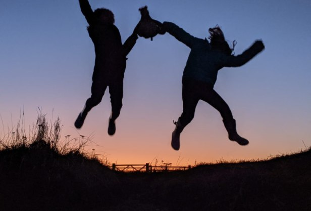 Two children in silhouette against a sunset sky jumping in the air off a sand dune