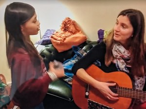 Child and woman signing while woman plays guitar