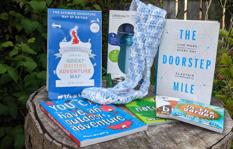 Giveaway prize selection of books, map, water bottle and crocheted bottle holder on log