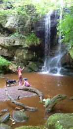 Children and dog by waterfall