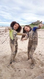 two-girls-in-westuits-covered-in-sand-being-zombies-on-the-beach-with-castle-in-background