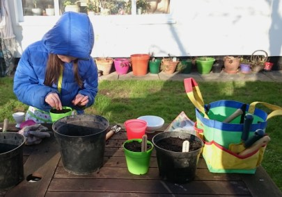 girl-in-blue-coat-potting-seeds-on-table-in-garden