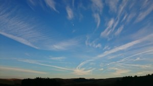 moon-and-con-trails-in-evening-sky-over-silhouetted-landscape