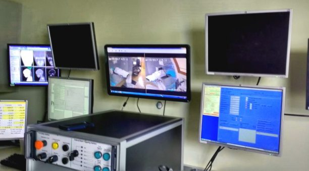 Panel of computer screens on wall showing radiotherapy treatment room via CCTV camera