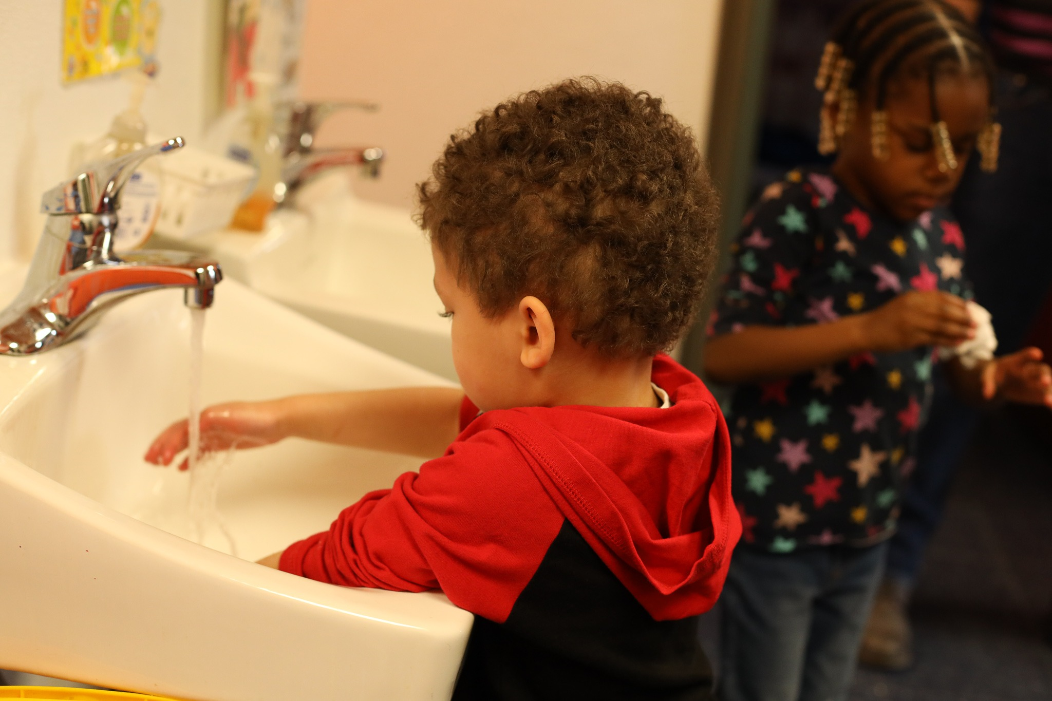Child washing hands in the sink