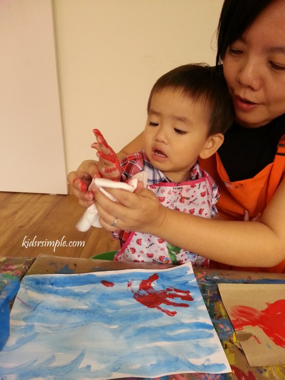 Getting his hand smeared with red paint