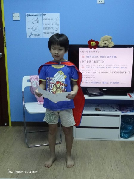 My boy wearing a cape and reading to the class.