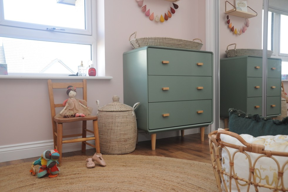 baby girl changing station on top of green chest of drawers
