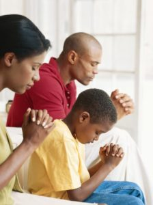 Parents with son (6-9) praying, side view