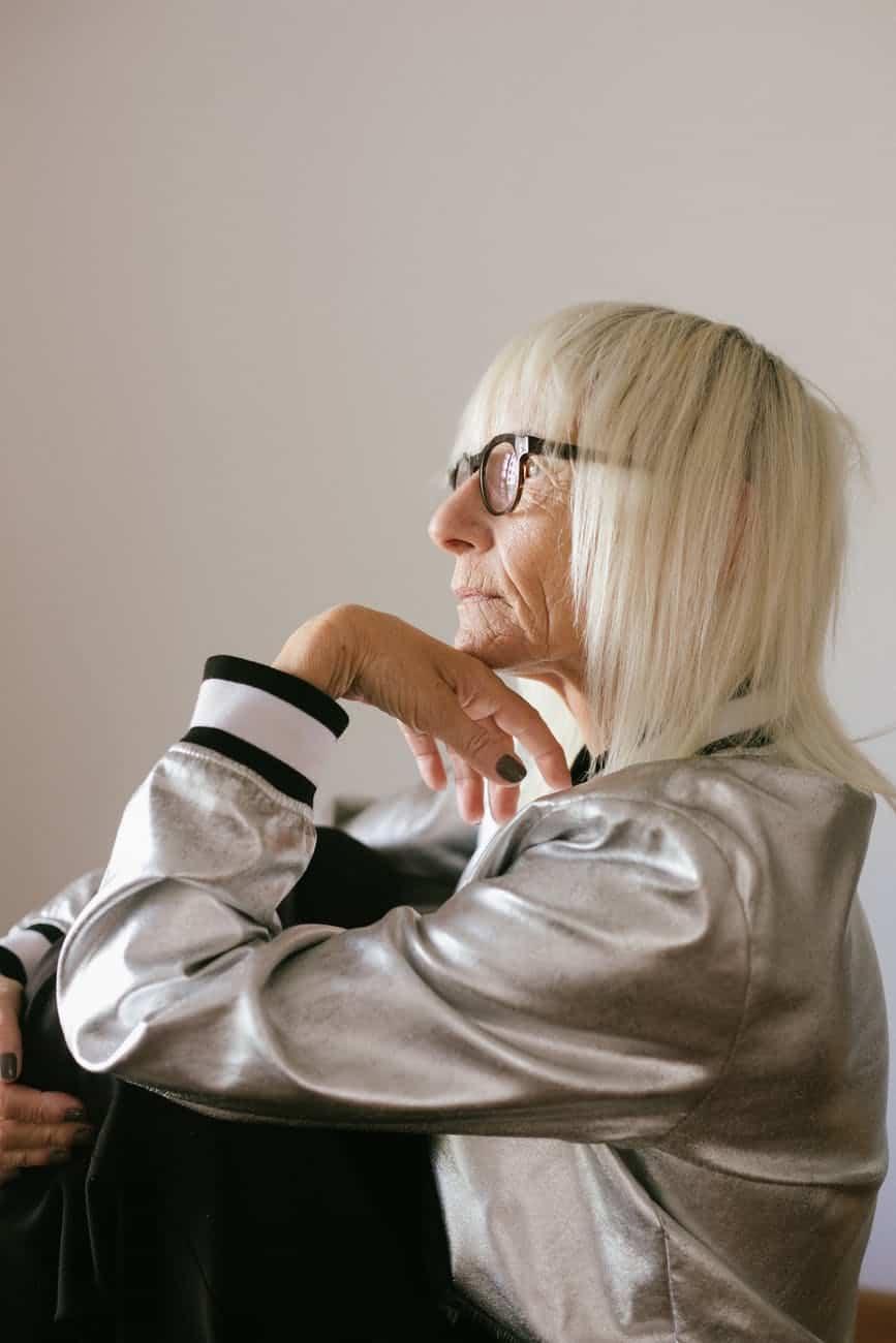 pensive elderly woman in eyeglasses and trendy bomber