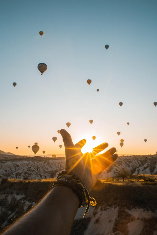 https://www.pexels.com/photo/photo-of-person-s-hand-across-flying-hot-air-balloons-during-golden-hour-2893685/