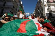 People carry their national flags as they protest over President Abdelaziz Bouteflika's decision to postpone elections and extend his fourth term in office, in Algiers, Algeria March 15, 2019. REUTERS/Zohra Bensemra - RC15B30BA7A0