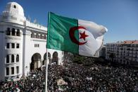 An Algerian flag flutters as people gather during a protest over President Abdelaziz Bouteflika's decision to postpone elections and extend his fourth term in office, in Algiers, Algeria March 15, 2019. REUTERS/Zohra Bensemra - RC15B900A580