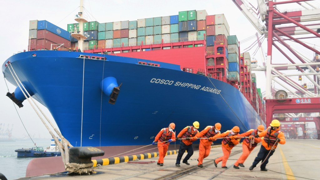 Workers wearing face masks rope a container ship at a port in Qingdao, Shandong province, China February 11, 2020. Picture taken February 11, 2020. China Daily via REUTERS  ATTENTION EDITORS - THIS IMAGE WAS PROVIDED BY A THIRD PARTY. CHINA OUT. - RC2UYE97AHZW