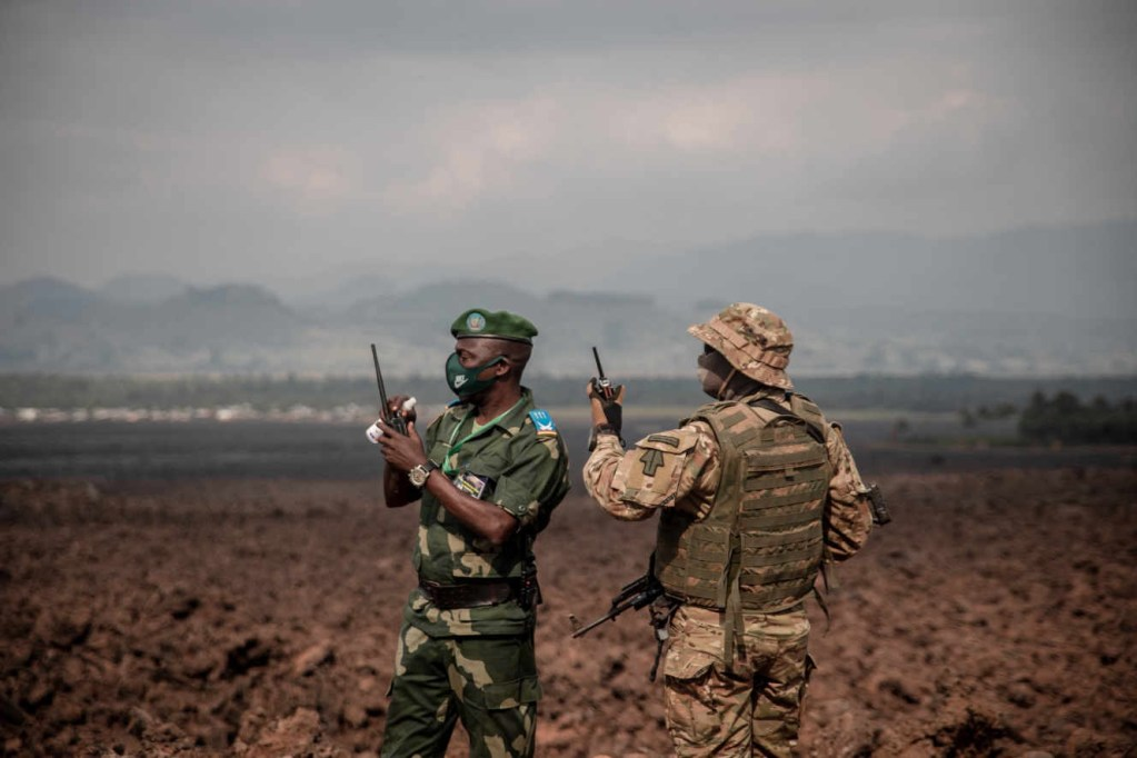 Two military stand guard on the solidified lava flow during a visit by Democratic Republic of Congo President Felix Tshisekedi to Goma, the provincial capital of North Kivu, on June 14, 2021. - The president visited Goma stricken by the eruption of the Nyiragongo volcano on May 22, 2021 which caused the death of about thirty people and the evacuation of nearly half a million people. (Photo by GUERCHOM NDEBO / AFP)