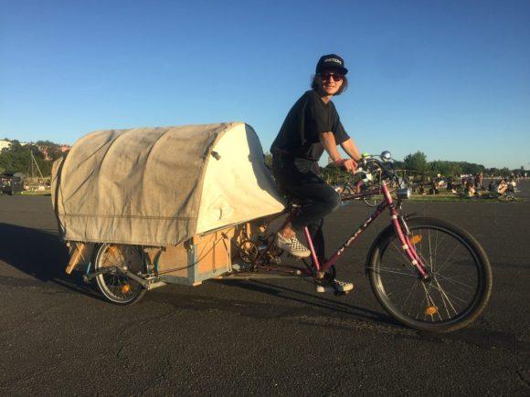 Stefanie de Velasco sitzt auf ihrem selbstgebauten Lastenrad. Hinter dem Sattel ist ein angebauter Anhänger im Stil eines Planwagens.