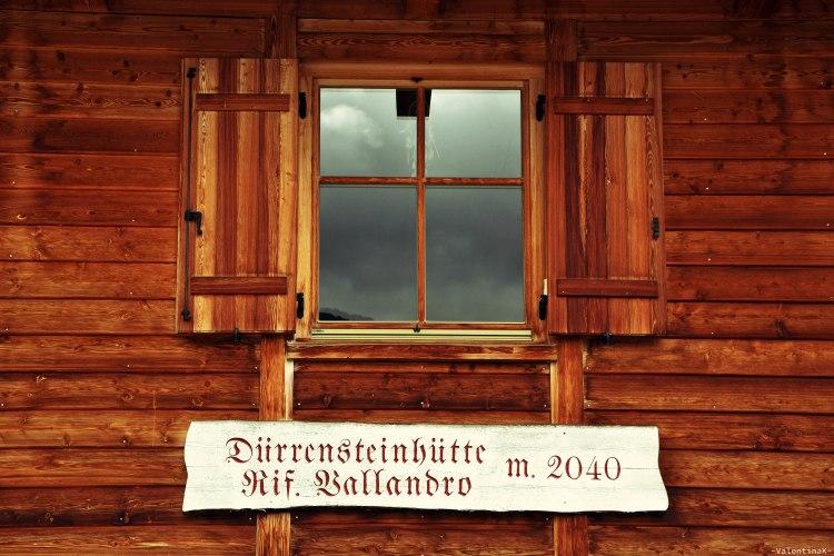 Il rifugio vallandro e le sue finestre che riflettono un temporale in arrivo