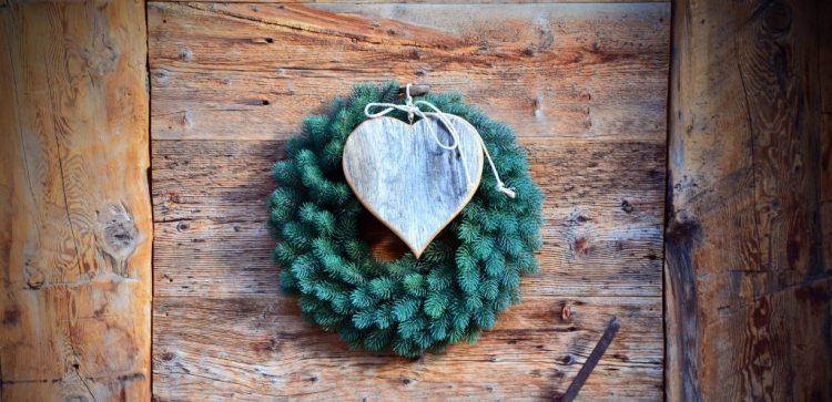 lista di rifugi in Alta Badia: foto di cuore di legno e ghirlanda su porta di legno grezzo