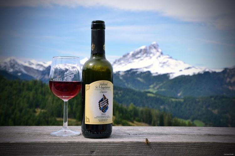 rifugi in val badia: calice di vino santa magdalena con bottiglia, e sas de putia innevato sullo sfondo