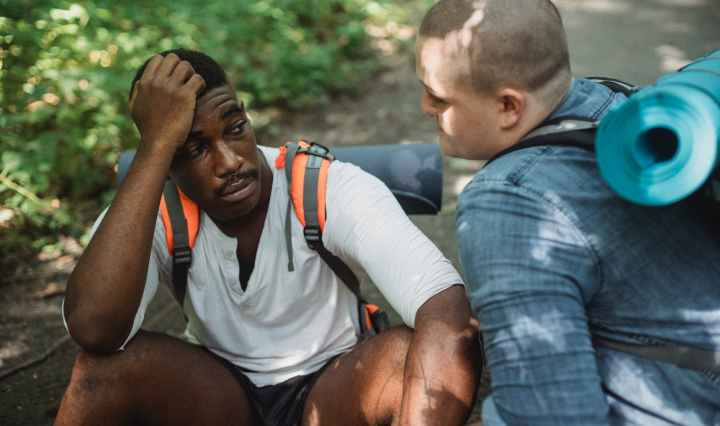 frustrated black man talking to friend while travelling together