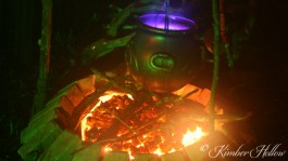 A cauldron of potion simmers over red hot coals