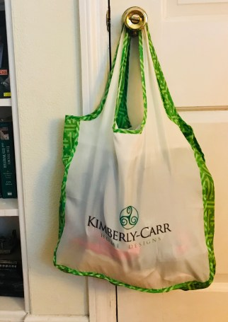 a reusable cloth grocery bag with the Kimberly-Carr Home Designs logo. Cloth bags keep us plastic-free on grocery day.