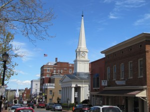 a street view with brick buildings and a white building with a steeple