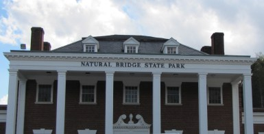 """a red brick building with white pillars and """"Natural Bridge State Park"""" across the top"""