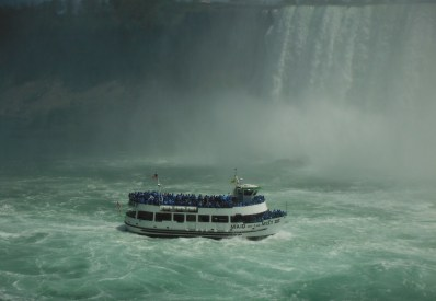 ferry boat in front of falls surrounded by mist