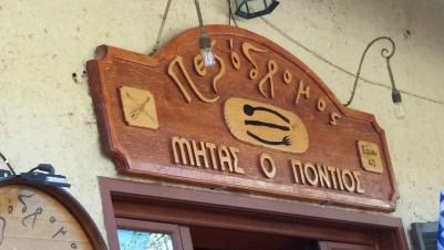 Sign over a door in Greek naming the restaurant