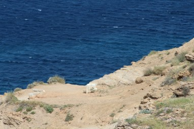 a white stone embedded in the earth next to a cliff on the edge of the sea