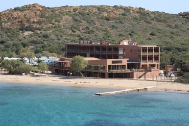 A four story hotel on the beach with a mountain behind