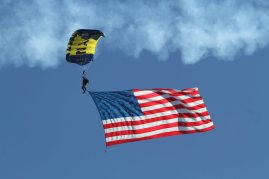 A member of the Navy Leap Frogs Parachute Team unfurls an American Flag. San Francisco Fleet Week 2015