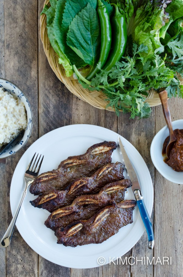grilled short kalbi ribs on plate with side of ssamjang, ssam greens and rice