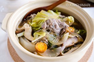 Bulgogi Hot Pot (Jeongol) served in white clay pot with wooden spoon